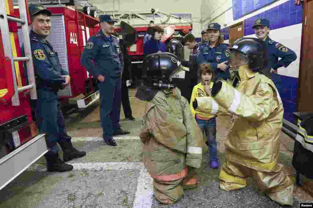 Trẻ em chạy lánh chiến sự ở khu vực phía đông Ukraine mặc quần áo lính cứu hỏa trong một chuyến tham quan đến một trạm cứu hỏa ở Krasnoyarsk, Nga.
