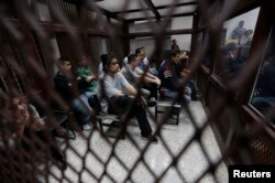 FILE - Members of a gang sit behind bars at a court that deals with gender-based crimes in Guatemala City, July 3, 2013.