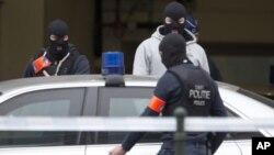Cảnh sát Bỉ bước vào một chiếc ôtô đỗ bên ngoài một tòa án nơi Salah Abdeslam, nghi can chính trong vụ đánh bom ở Paris năm ngoái, dự kiến trình diện trước một thẩm phán ở Brussels hôm 24/3.