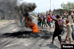 FILE – In January 2015, demonstrators burned tires to set up barricades during a protest over proposed changes to an election law in the Democratic Republic of Congo's capital Kinshasa.