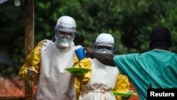在塞拉利昂,医务人员给被隔离的埃博拉病人送饭 。