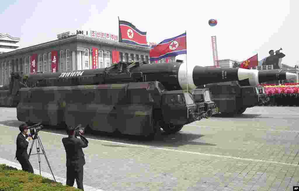 """导弹车参加阅兵式,通过平壤金日成广场(2017年4月15日)。 军事专家说,这个导弹似乎是洲际弹道导弹。台湾 """"军情与航空""""网站主编施孝玮对美国之音说,这次阅兵具有一些实质看点,""""展示了他们的最新式弹道导弹。朝鲜核威慑的力量确实越来真实,而且波及到北美洲。看得出来,美国和北朝鲜剑拔弩张,而且双方的筹码越来越高""""。"""