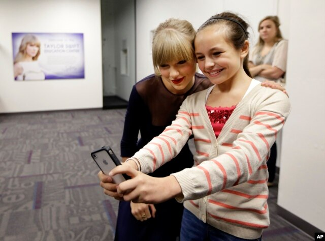 Taylor Swift poses for a photo with Piper Moralez, 11, at the Country Music Hall of Fame and Museum, Oct. 12, 2013, in Nashville, Tenn. Swift is at the facility to open the $4 million Taylor Swift Education Center.
