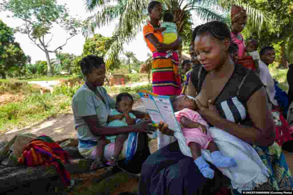 Mulher lê caderneta de saúde do seu filho durante uma sessão de vacinação em Kabea Kamwanga.