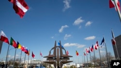 The NATO symbol and flags of the NATO nations outside NATO headquarters in Brussels on Sunday, March 2, 2014. NATO is calling emergency talks on Sunday regarding the escalating crisis in Ukraine. (AP Photo/Virginia Mayo)