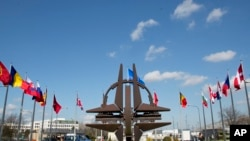 Biểu tượng của NATO và cờ của các quốc gia NATO bên ngoài trụ sở chính ở Brussels.