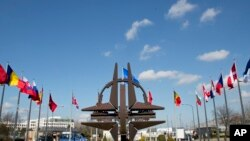 FILE - The NATO symbol and flags of the NATO nations outside NATO headquarters in Brussels, March 2, 2014. Officials from NATO and Russia are scheduled to hold their first formal meeting in almost two years, covering Ukraine, the security situation in Afghanistan, and military activities, the Western alliance said Tuesday.