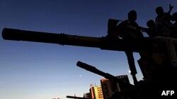 Libijski mladići sede na topu uništenog vojnog tenka u Misrati.