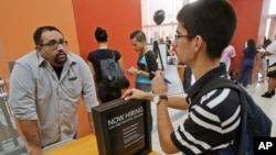 Anh Lazaro Fonte (phải), 24 tuổi, nói chuyện với trợ lý quản lý của thương hiệu Banana Republic Edward Ortega trong một hội chợ việc làm tại Dolphin Mall ở Miami.