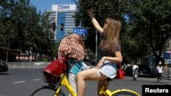 2018年8月29日,在北京中兴通讯公司大楼附近,一名女子自拍。