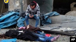 This photo provided by the Syrian Civil Defense White Helmets, which has been authenticated based on its contents and other AP reporting, shows a Syrian boy sitting next to bodies after artillery fire struck the Jub al-Quba district in Aleppo, Syria, Nov.