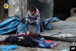 This photo provided by the Syrian Civil Defense White Helmets, which has been authenticated based on its contents and other AP reporting, shows a Syrian boy sitting next to bodies after artillery fire struck the Jub al-Quba district in Aleppo, Nov. 30m, 2016.