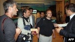 "Novinari agencije Frans pres, Roberto Šmit (centar) i Dejv Klark (drugi desno), kao i fotoreporter ""Geti imidžes"" Džo Ridle (levo) daju izjavu u Tripoliju neposredno posle oslobađanja, 23. mart 2011."