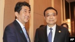 2016年7月15日,日本首相安倍晋三与中国总理李克强在蒙古乌兰巴托举行的亚欧峰会期间举行双边会谈前握手。