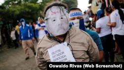 បាតុករម្នាក់ដែលពាក់ស្រោមមុខលោកប្រធានាធិបតីនីការ៉ាហ្គា Daniel Ortega ចូលរួមនៅក្នុងការដើរក្បួនមួយដើម្បីគាំទ្រដល់ព្រះវិហារកាតូលិក នៅក្នុងក្រុង León ប្រទេសនីការ៉ាហ្គា កាលពីថ្ងៃទី២៨ ខែកក្កដា ឆ្នាំ២០១៨។
