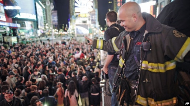 A firefighter waves to the crowd as people celebrate after Al Qaeda leader Osama bin Laden was killed in Pakistan, during a spontaneous celebration in New York's Times Square, May 2, 2011