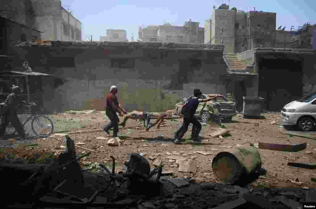 បុរសៗប្រមូលសាកសពនៅកន្លែងវាយប្រហារតាមអាកាសនៅក្នុងសង្កាត់ Douma ដែលគ្រប់គ្រងដោយក្រុមឧទ្ទាម ក្នុងប្រទេសស៊ីរី កាលពីថ្ងៃទី២៥ ខែកក្កដា ឆ្នាំ២០១៦។
