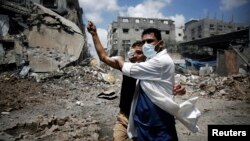 Seorang petugas medis membantu seorang warga Palestina di daerah Shejaia yang dibombardir tembakan oleh Israel, di Gaza City (20/7). (Reuters/Finbarr O'Reilly)