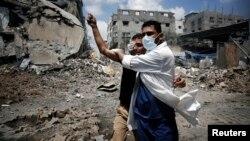 Binh sĩ cứu thương giúp một người Palestine bị thương trong vụ không kích của Israel tại Shejaia, thành phố Gaza, ngày 20/7/2014.