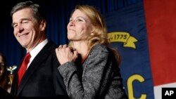 FILE - North Carolina Democratic candidate for governor Roy Cooper and his wife, Kristin, greet supporters during an election night rally in Raleigh, N.C., Nov. 9, 2016.