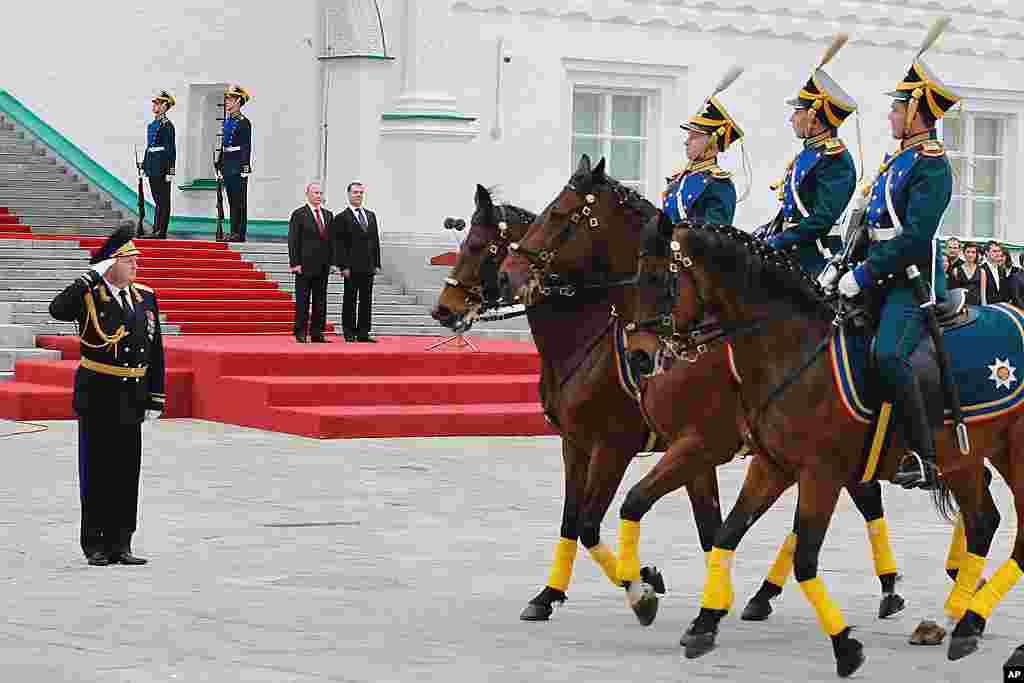 ທ່ານ Vladimir Putin ກັບອະດີດປະທານາທິບໍດີ Dmitry Medvedev ຢືນຊົມການສວນສະໜາມຂອງກອງກຽດຕິຍົດຂອງວັງ Kremlin ທີ່ຈະຕຸລັດ Cathedral Square ຫລັງຈາກພິທີສາບານໂຕ. (AP)