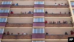 Les résidents confinés du quartier Hillbrow du centre-ville de Johannesburg sur leurs balcons le 27 mars 2020.