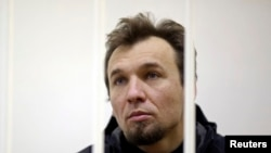 Greenpeace activist Tomasz Dziemianczuk of Poland looks out from a defendants' cage during a court session in St. Petersburg, Russia, Nov. 19, 2013.