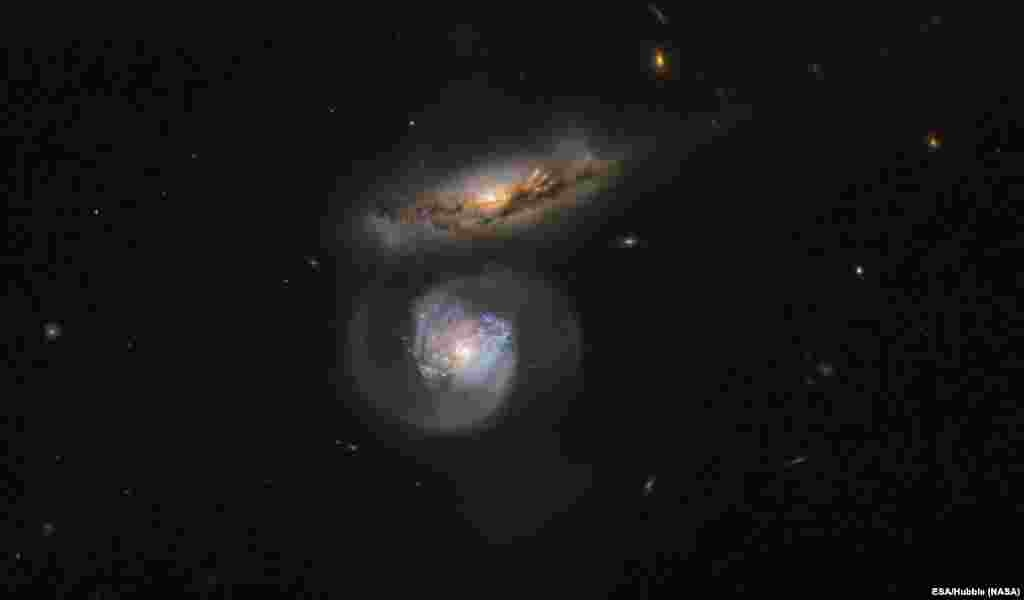 The galaxy named MCG+01-38-005 (the lower, blue-tinted one) is a special kind of megamaser and its active galactic nucleus pumps out huge amounts of energy, which stimulates clouds of surrounding water.