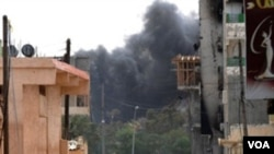 Dua tentara pemberontak Libya terlihat di jalanan Misrata. Asap dari serangan roket masih mengepul di kota ini, Minggu (24/4).