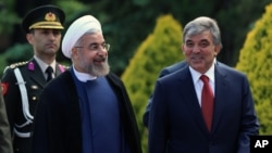 Turkey's President Abdullah Gul, right, and his Iranian counterpart Hassan Rouhani speak as they walk together during a ceremony at the Cankaya Palace in Ankara, Turkey, June 9, 2014.