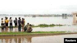 지난해 7월 북한 평안남도 안주에서 주민들이 폭우로 잠긴 농경지와 마을을 바라보고 있다.