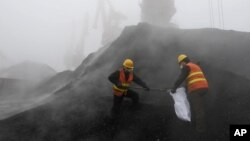 FILE - Employees from the local Entry-Exit Inspection and Quarantine Bureau collect samples of coal at a port in Rizhao, Shandong province.