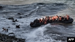 Refugees and migrants try to reach the shore on the Greek island of Lesbos, despite a rough sea, after crossing the Aegean Sea from Turkey, Oct. 30, 2015.