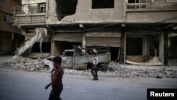 Children walk near damaged buildings in rebel-held Ain Tarma, eastern Damascus suburb of Ghouta, Syria, September 17, 2016.