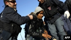 Cảnh sát Ý giúp đỡ 1 người đàn ông chạy trốn khỏi Tunisia sau khi đến đảo Lampedusa, Ý, 24/3/2011