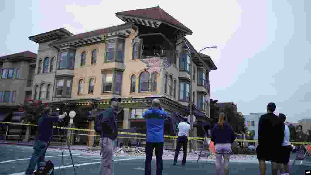 People look at a damaged building with a top corner exposed following an earthquake in Napa, California, Aug. 24, 2014.