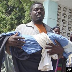 Un père portant le corps sans vie de son enfant à Mogadiscio