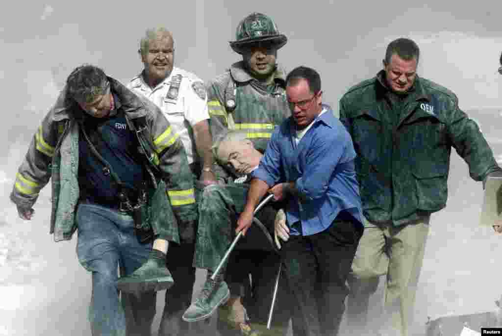 Un homme mortellement blessé est porté par une équipe de secouristes à New York, le 11 septembre 2001.