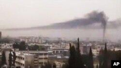 ຮູບຖ່າຍຂອງມື້ກ້ອງສະມັກຫຼິ້ນ ທີ່ພິມເຜີຍແຜ່ໂດຍຕາໜ່າງຂ່າວ Shaam ສະແດງໃຫ້ເຫັນວ່າ ມີຄວັນສີດຳກຸ້ມ ຂຶ້ນສູ່ທ້ອງຟ້າ ຈາກເມືອງ Homs ໃນເຂດພາກກາງຂອງຊີເຣຍ (16 ກຸມພາ 2012)