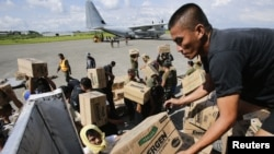 Philippine Army personnel unload relief goods to be transported to regions affected by Typhoon Bopha, from the Marine Corps KC-130J Hercules aircraft inside the International Airport in Davao, Mindanao December 15, 2012. United States Marines together wit