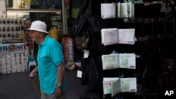 An elderly man walks past wallets designed as euro banknotes, outside a kiosk in central Athens, June 16, 2017. After months of haggling that raised fears of another escalation in Greece's debt crisis, the 19-country eurozone agreed late Thursday to clear