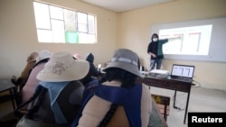 Parents attend a lesson on how to handle a smartphone for virtual home schooling for their children, during the coronavirus disease (COVID-19) outbreak, in El Alto, Bolivia July 12, 2021. Picture taken July 12, 2021. REUTERS/Claudia Morales
