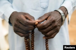 FILE - A Muslim holds Prayer beads outside a mosque in the town of Koui, Central African Republic, April 27, 2017.