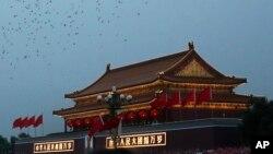 在国庆日的升旗式上,鸽子飞过天安门。(2014年10月1日)