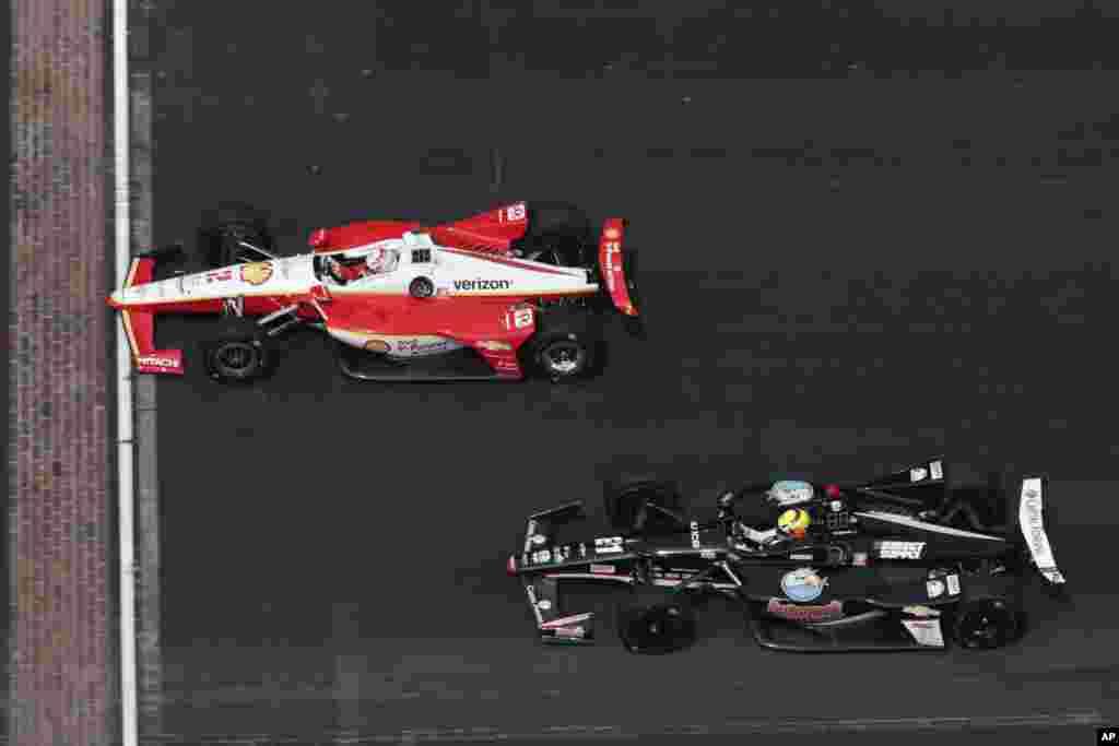 رقابت دو ماشین در تمرین در شهر ایندیاناپولیس در ایالت ایندیانا. این شهر در آمریکا میزبان مسابقات ماشین های سریع است.
