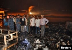 FILE - The governor of Sindh province, Ishrat ul Ebad, and security officials visit a damaged area after an attack on Jinnah International Airport in Karachi, Pakistan, June 9, 2014.