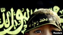 FILE - A boy stands before an Islamic jihad flag. Concern is growing in Germany and other countries that the Islamic State group, now largely weakened, is actively recruiting children to carry on their jihadist legacy.