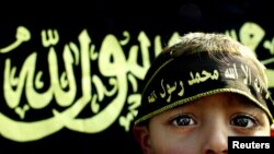 FILE - A boy stands before an Islamic jihad flag. Concern is growing in Germany and other countries that the Islamic State group, now largely weakened, has been recruiting children to carry on their jihadist legacy.