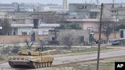 تانکێـکی حکومهتی سوریا له کۆڵانێـکی گهڕهکی ڕهستهنی شـاری حومس وهسـتاوه، دووشهممه 30 ی یهکی 2012