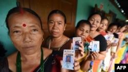 Warga membawa kartu identitasnya saat mengantre untuk memberikan suara dalam pemilihan umum lokal di Diphu, Nagaland. (Foto: Dok)